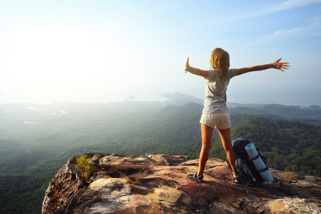 A woman stands on a cliff, arms outstretched towards the view
