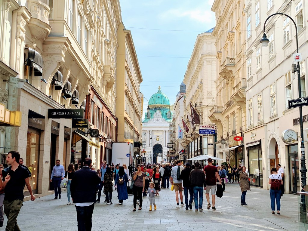 A street in Vienna, with people shopping and many luxury shops on the sides