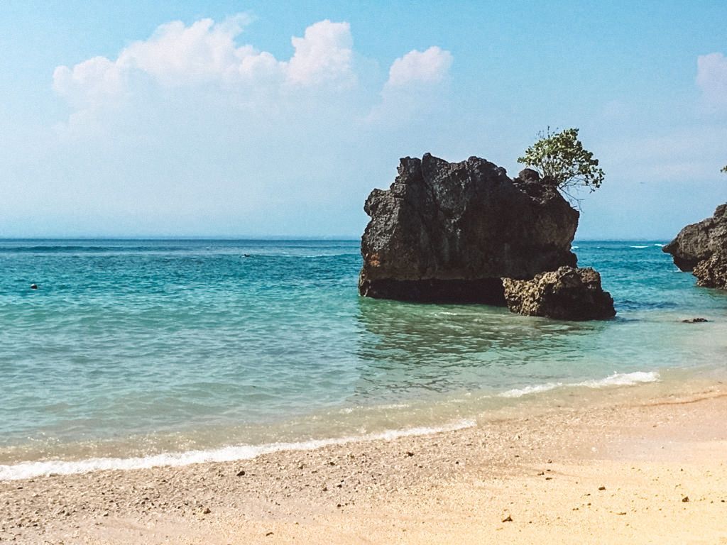 A rock formation located off a beach in Bali, Indonesia