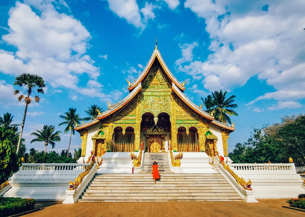 A woman standing in front of a temple in Luang Prabang. Laos is one of the most popular cheap countries to visit in Asia.