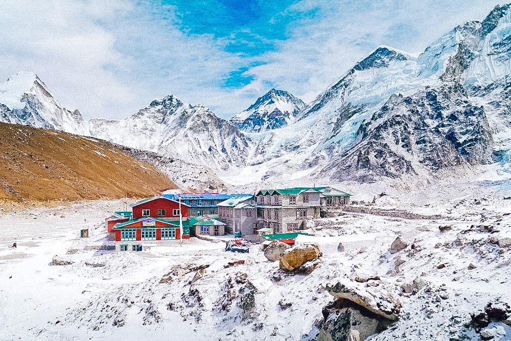 A building lies below a snowy mountain in Nepal, one of the cheap countries to travel in Asia