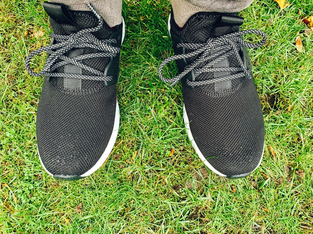 A pair of black waterproof sneakers on a grass lawn