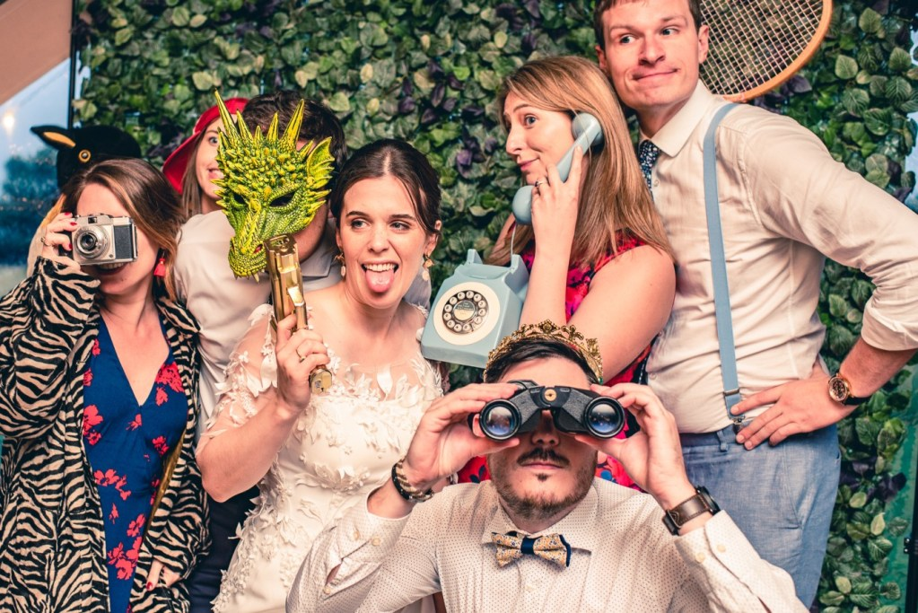 B&A wedding day - Oaktree farm outdoor wedding venue in nottinghamshire / lincolnshire - photobooth fancy dress group shot with binoculars, tennis racket, masks and phones