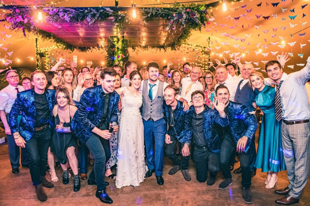 B&A wedding day - Oaktree farm outdoor wedding in nottinghamshire - group photo with the band on the dancefloor