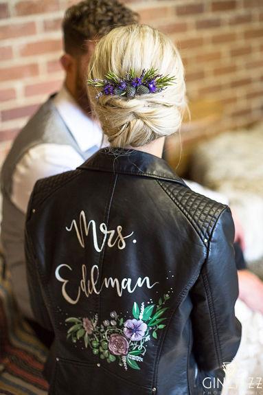 B&N barn wedding - bride wearing customised black bridal leather jacket sitting on haybale