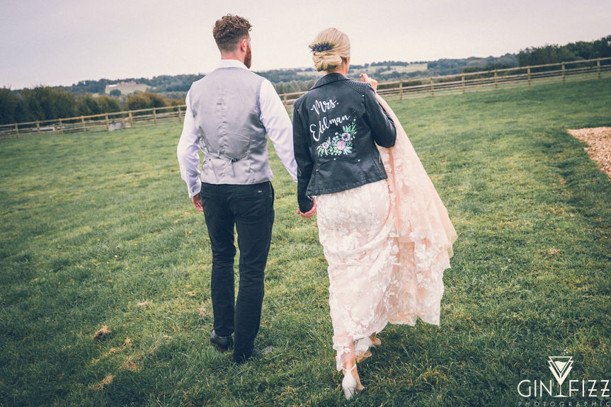 B&N outdoor wedding day castle view farm and stables leicestershire wedding venue - 2 bride and groom walking in the fields 4
