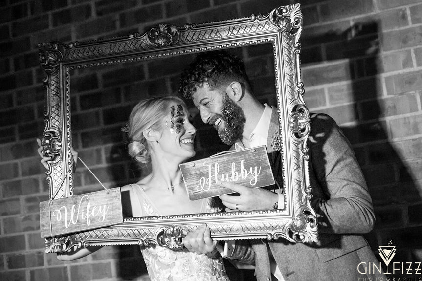 B&N wedding day castle view farm and stables old school photobooth hubby and wifey with large gold frame smiling with glitter 2