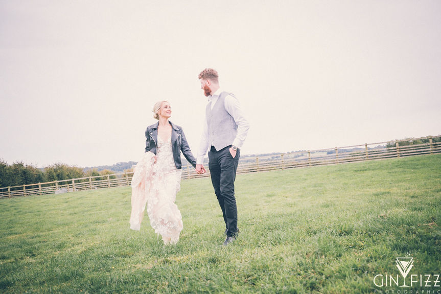 B&N outdoor wedding day castle view farm and stables leicestershire wedding venue - bride and groom walking in the fields