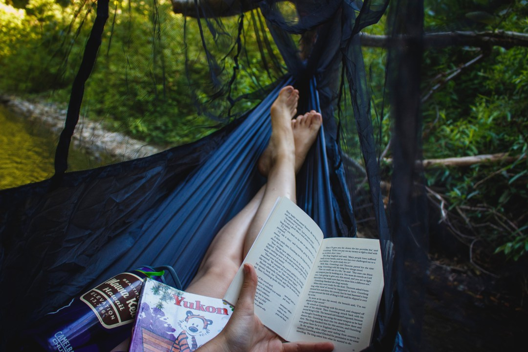 Reading a book while on a hammock.