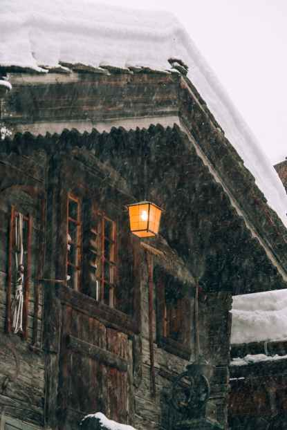 wooden cottage with burning lantern during snowfall