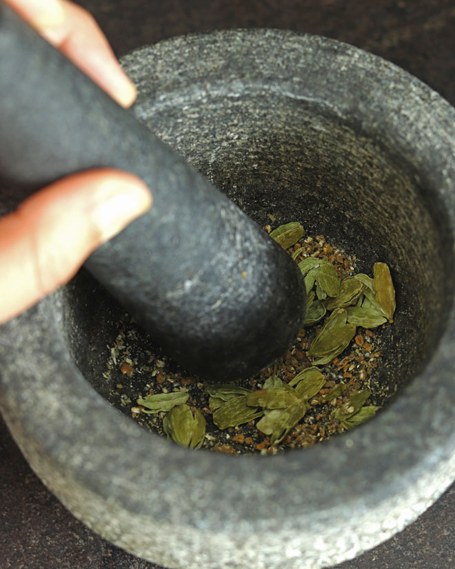 Crushing cardamom pods in a mortar and pestle to make Peanut Sweet Rice with coconut