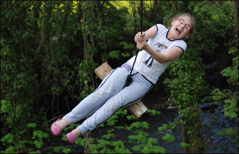 happy girl on a rope swing