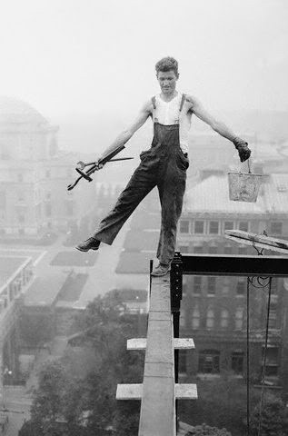 iron worker walking a beam high above the ground