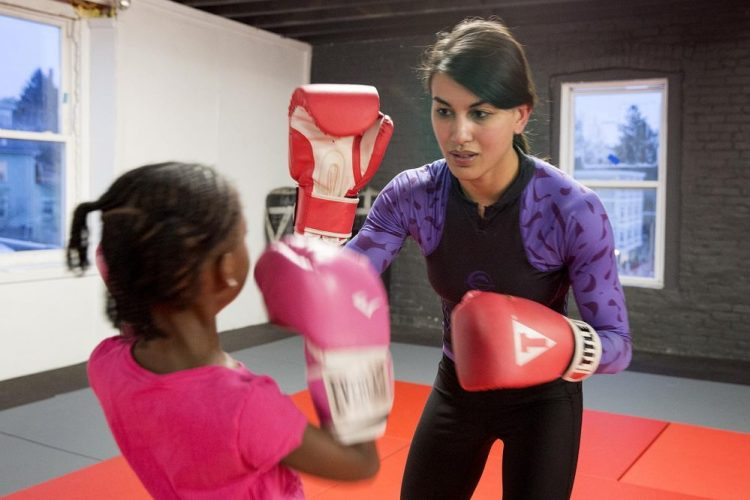 woman teaching child how to box