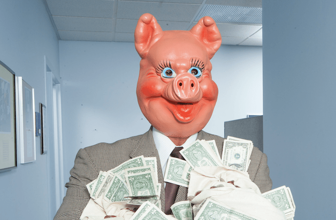 greedy man wearing pig face mask business suit cash money