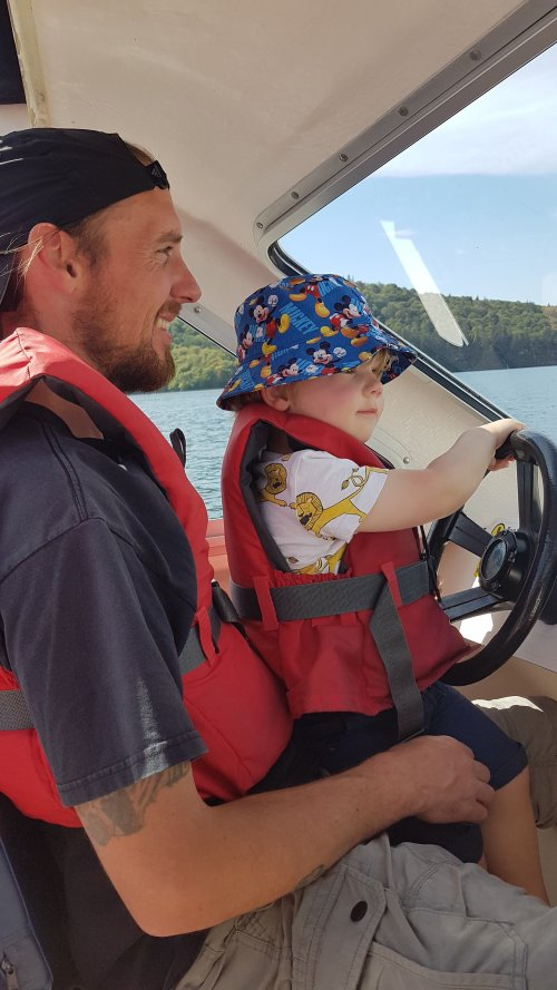 Toddler driving a boat