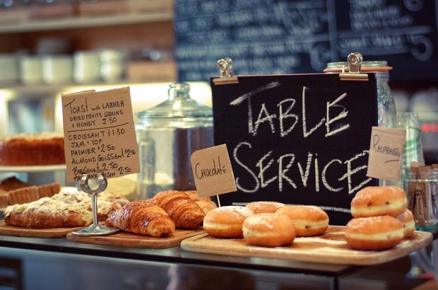 croissants and donuts on display in front of a table service sign