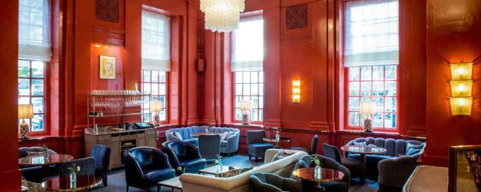 plush cafe bar in the bloomsbury hotel with comfortable sofas, coral coloured walls and a chandelier