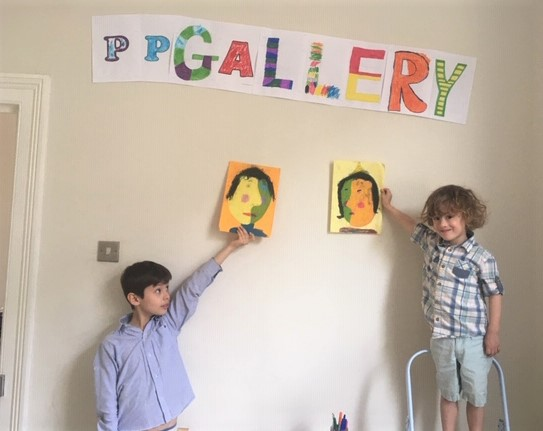 two boys holding up their drawings under the Portrait Party Gallery sign