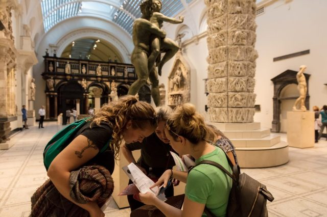 3 people look at a printed document, surrounded by statues in the V&A museum