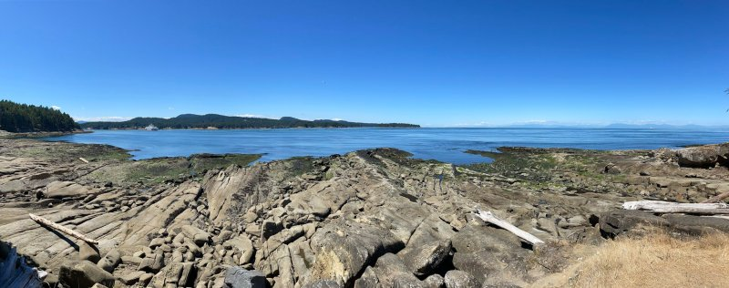A view of the ocean from a rocky shore on a sunny day with blue skies, with an island across an inlet and the mainland faintly visible in the distance.