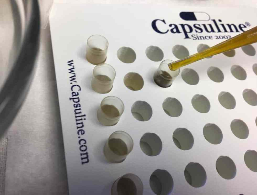 Filling capsules with infused oil for cannabis microdosing.