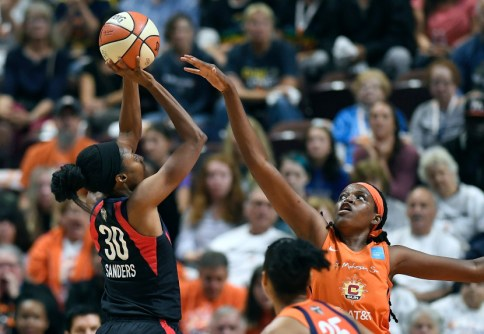 Washington Mystics' LaToya Sanders, left, shoots against Connecticut Sun's Jonquel Jones, right, during the first half in Game 3 of basketball's WNBA Finals, Sunday, Oct. 6, 2019, in Uncasville, Conn. (AP Photo/Jessica Hill)