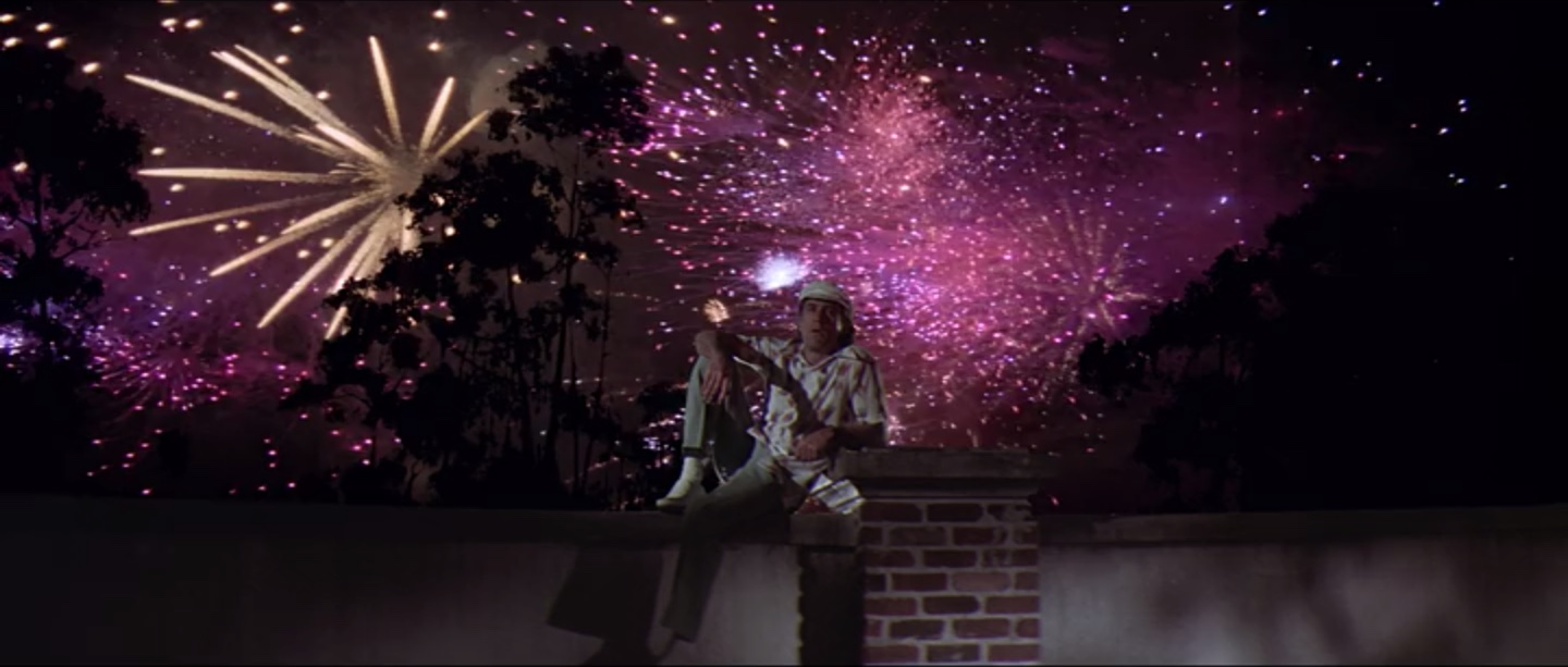 Robert De Niro as Max Cady sitting on a wall with fireworks in the background in Cape Fear