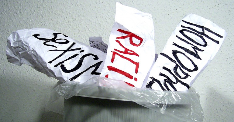 A photo of banners representing various forms of hate speech and hate crime that have been placed in a bin.