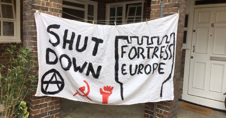 "A photo of a banner with the text ""Shut Down Fortress Europe"" written on it."