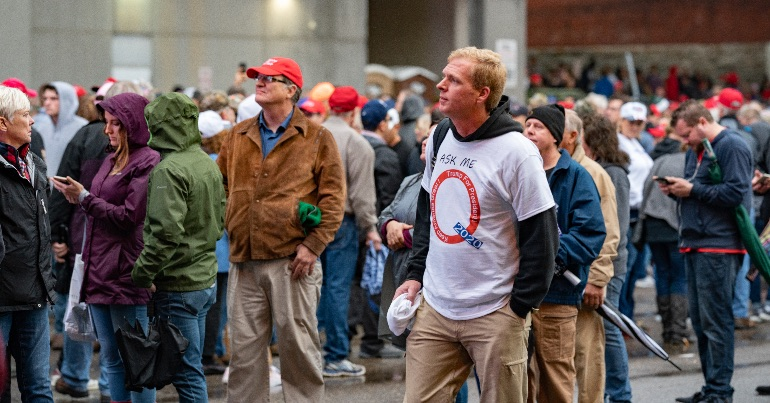 A photo of a Donald Trump supporter wearing a QAnon t-shirt.