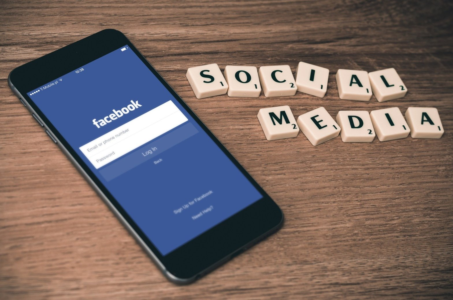 "image of letter tiles spelling out the words ""social media"" to the right of a smart phone with the Facebook login page"