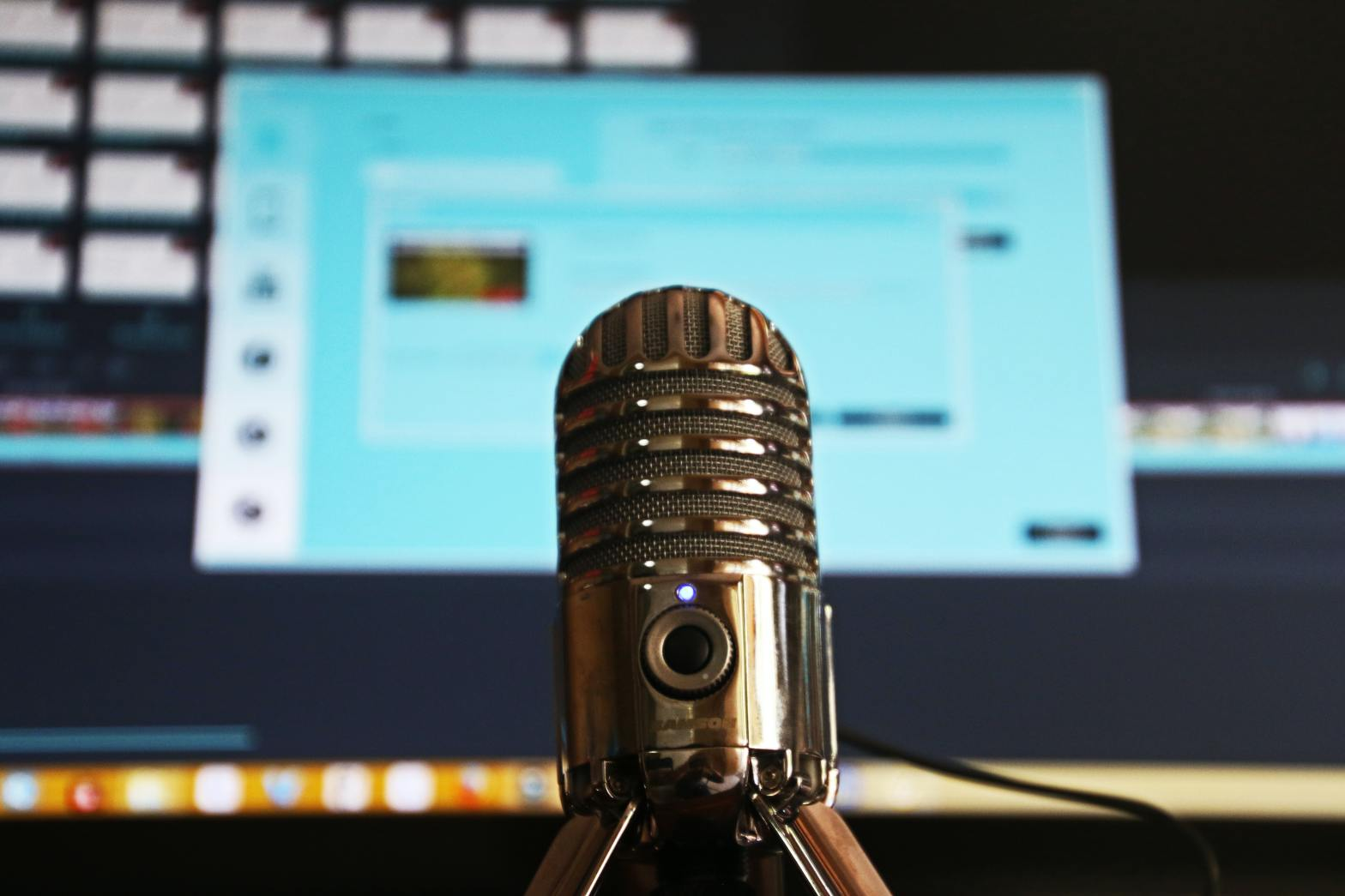 image of microphone in front of a computer monitor