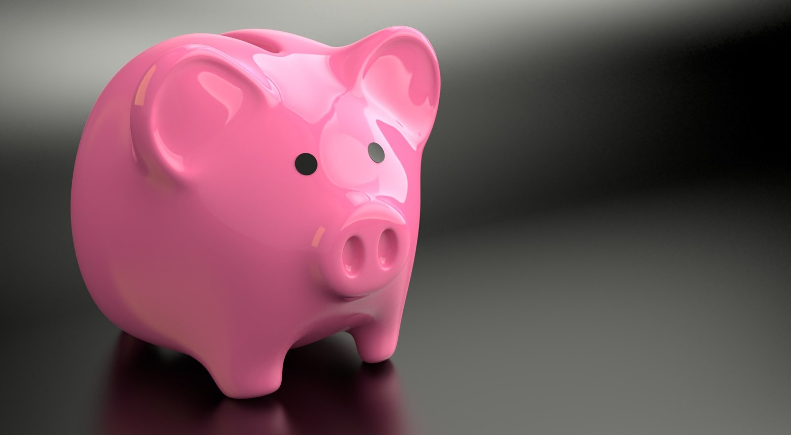 image of a pink piggy bank with a grayish black gradient background.