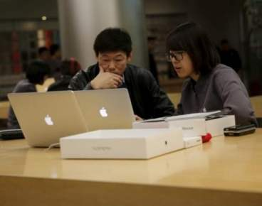 A female staff member assists a customer at an apple store in Beijing, November 2, 2015. REUTERS/Kim Kyung-Hoon