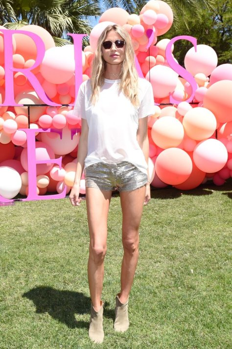 Martha Hunt wearing a white tee, Smoke x Mirrors sunglasses, and jean shorts at the Victoria's Secret Angel Oasis.