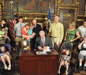 "Caption: Minnesota Governor Mark Dayton signs Leo's law to declare one week in September to ""Mitochondrial Disease Awareness Week"";  Image Credit: Mark Dayton - wikimedia"