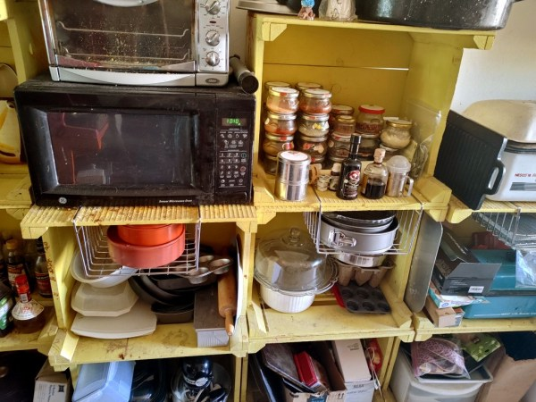 Microwave, Nesco roaster oven, and baking supplies. The stacked jars have frequently used spices in them.