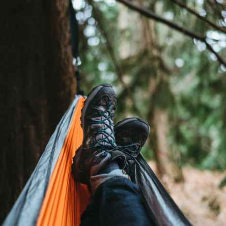 person wearing pair of black hiking shoes lying on orange and gray hammock