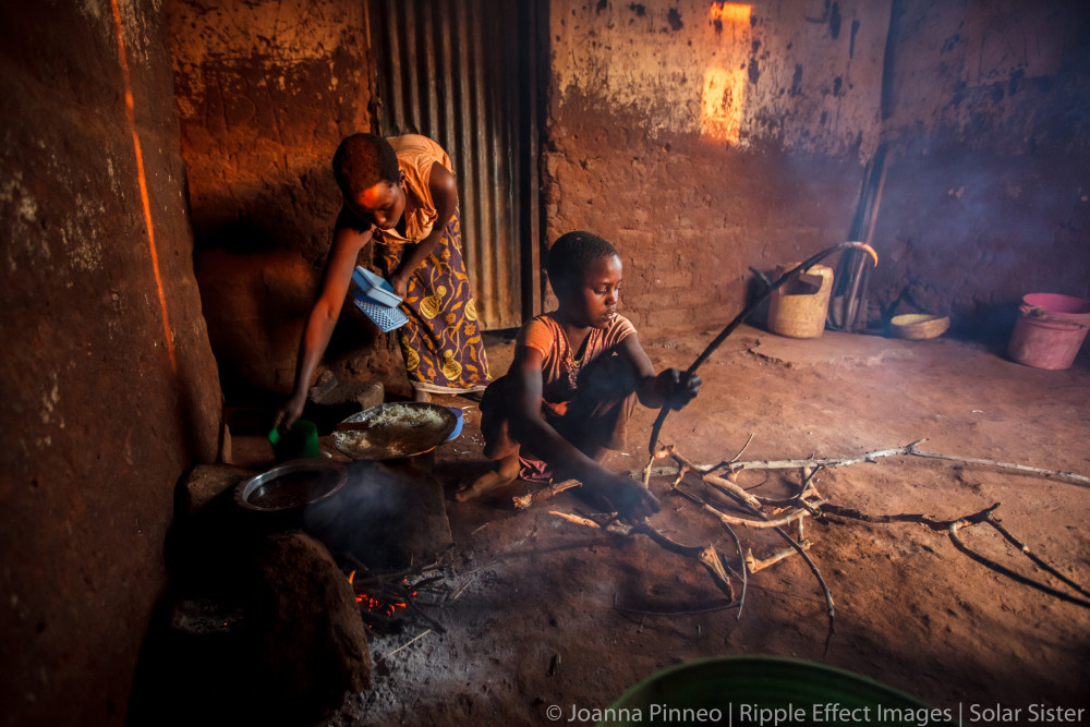 Ester Hodari, age 22 years old, cooks dinner using the traditional three-rock cook stove.