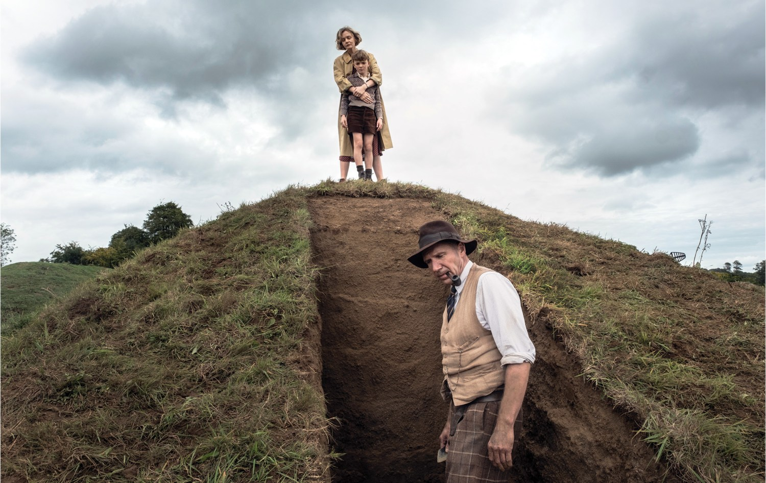 above Ralph Fiennes as Basil Brown, Carey Mulligan as Edith Pretty, and Archie Barnes as her son Robert, at the recreated Sutton Hoo mound in The Dig. right Ben Chaplin and Lily James play archaeologists Stuart and Peggy Piggott.