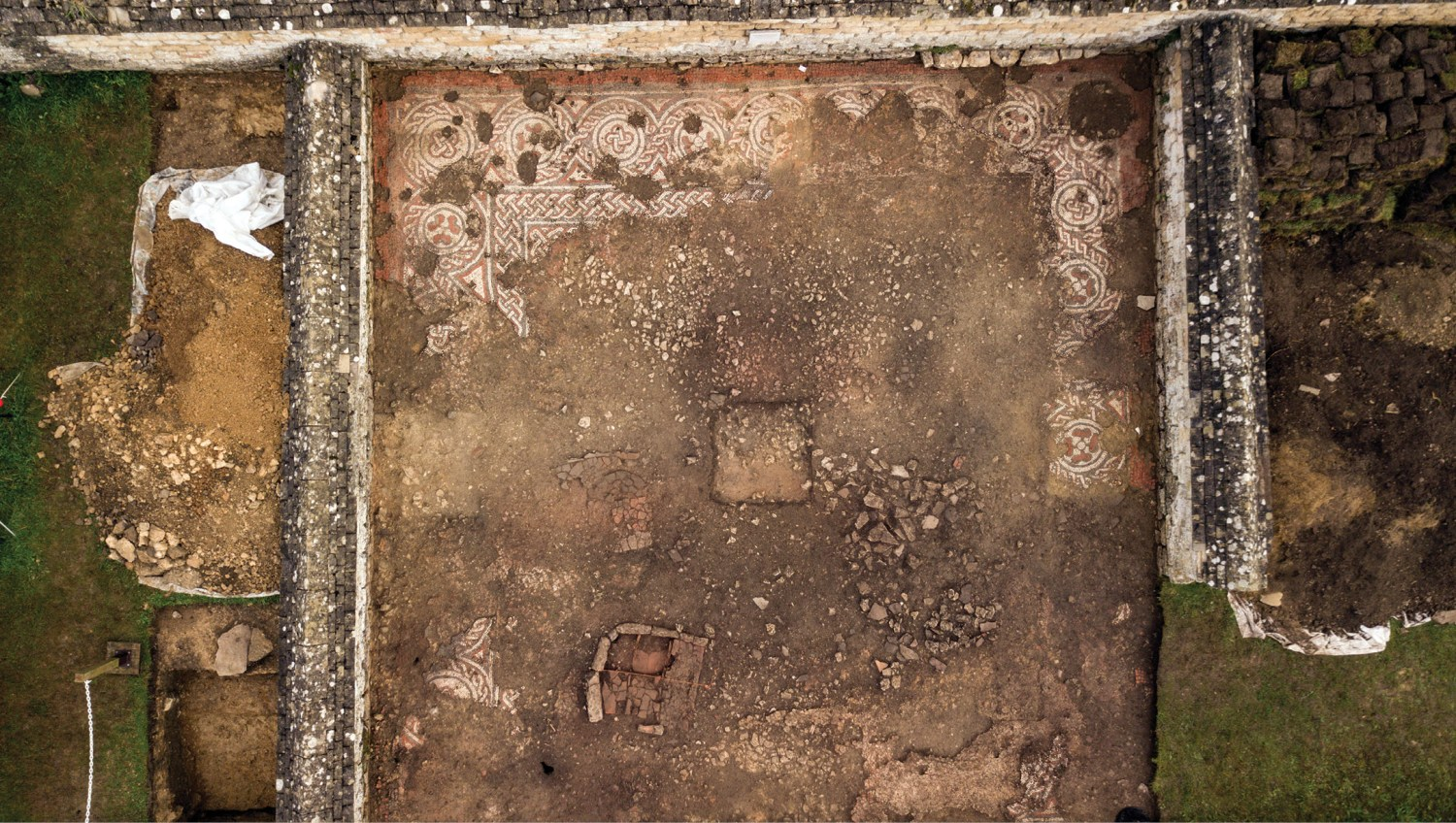 below Only fragments of Room 28's once-grand mosaic survive today. On the left side of the photograph, the trenches opened in Room 27 can be seen; meanwhile, turfs from the excavation have been stacked in Room 29 on the right.