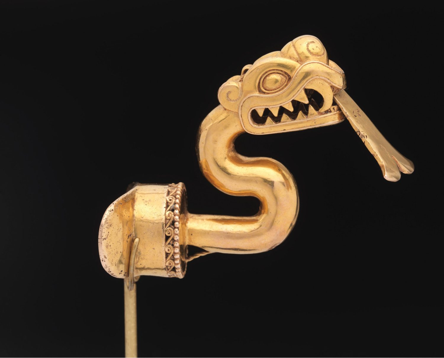 below Aztec labret (jewellery worn in a piercing below the lower lip) in the form of a serpent with an articulated tongue, from Mexico. Gold, AD 1300-1521. Size: 6.67 x 4.45 x 6.67cm