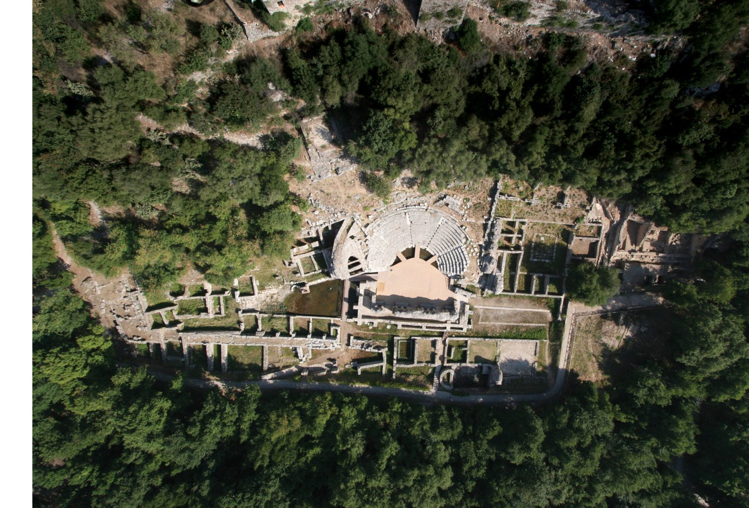 BELOW Aerial photograph of the W Courtyard and Theatre at Butrint. A shrine of Asklepios is visible just beyond the theatre, at the point where the seating terminates at the entrance. The compitum, round altar and pedestal of Aulus Granius, honorific bench, and water basin can be made out directly beyond the shrine, where standing water is visible in the photograph.