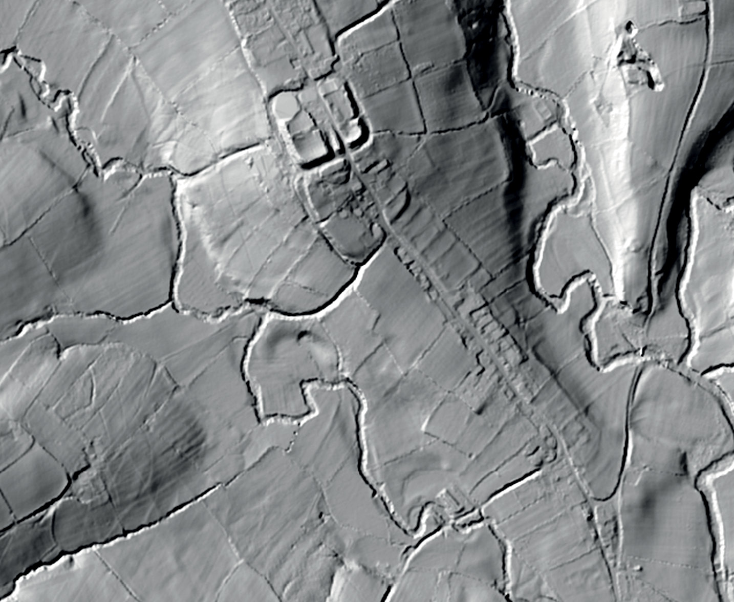 below Surviving earthworks flank the single street of Longtown, marking strip fields, the medieval market place, burgage plots, and meadows.