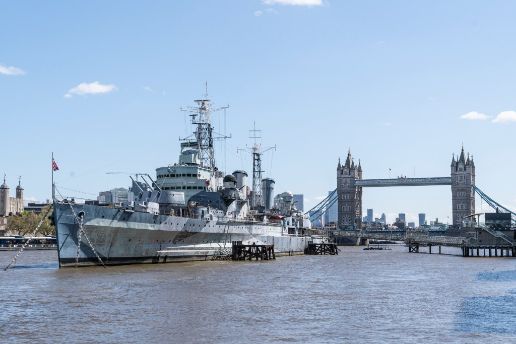 HMS Belfast in front of Tower Bridge, at its home on the Thames. Image: IWM.