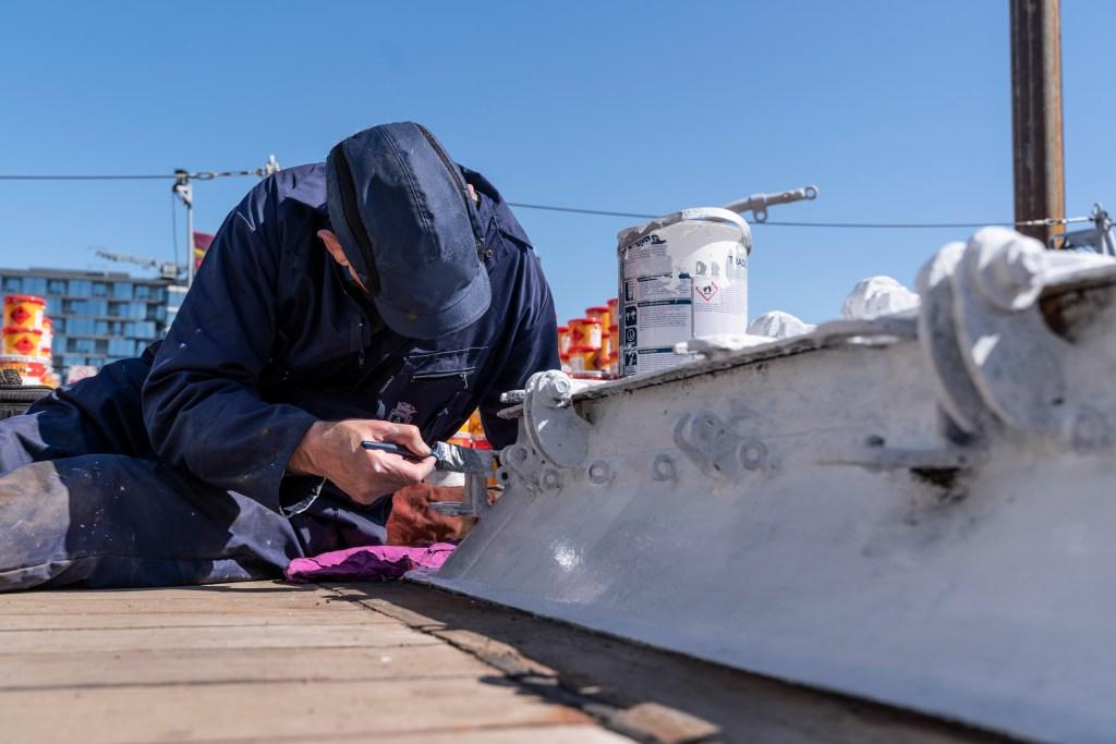 HMS Belfast undergoing repainting work. Image: IWM.
