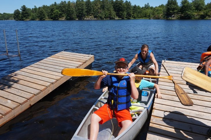 A photo of two children in a canoe, with a counsellor pushing off from the dock.