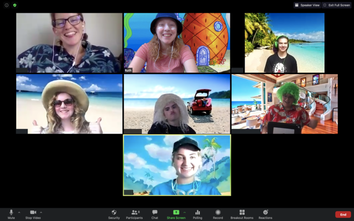 Seven young people pose on Zoom. They are dressed for the beach with artificial beach background edited behind them.