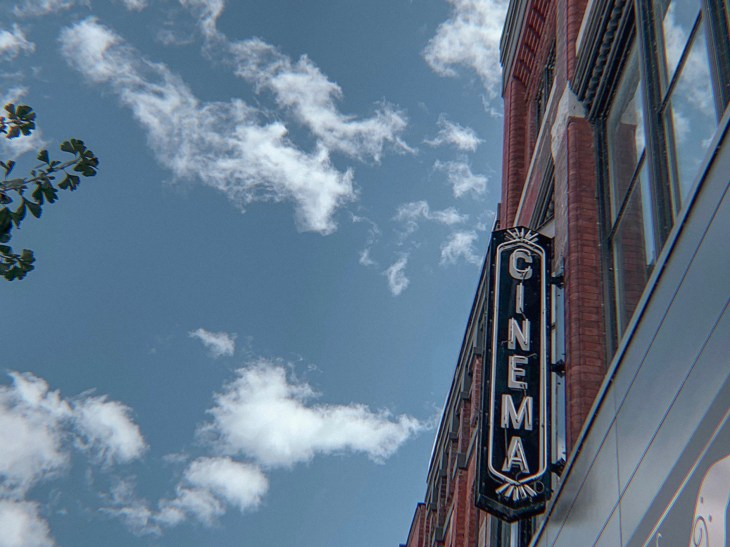 """A photo of a sign affixed to a brick building reading """"cinema""""."""